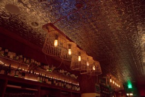 Pressed tin ceiling glows w/ artful lighting