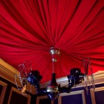 Red velvet-draped ceiling with vintage fans at Big