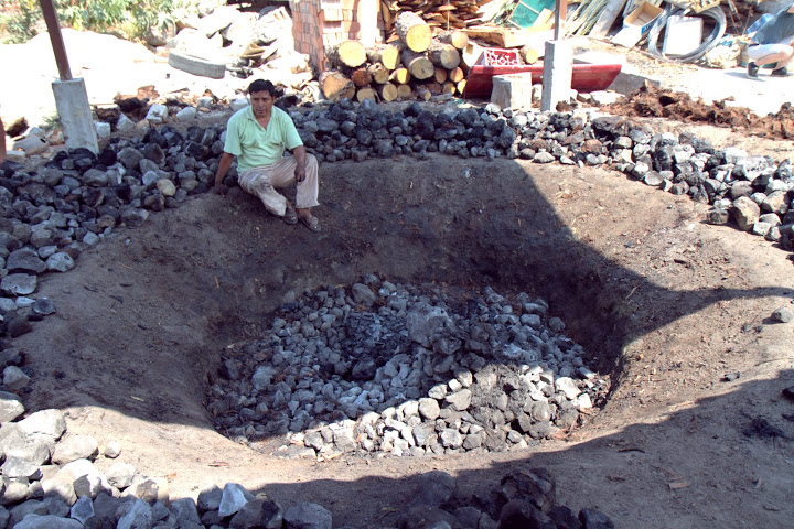 Roasting agave in a pit
