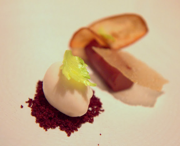 Dessert of pear sorbet over chocolate crumbs, topped with a celery leaf, next to walnut croquant & chocolate cremeaux