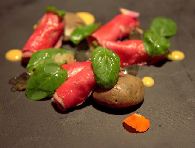 Bluefin tuna sashimi wrapped in veal tongue pastrami, peach kimchi sauce, algae, lotus salad